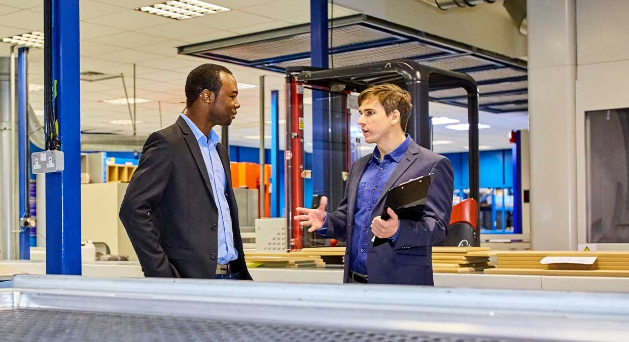 Two people talking on a manufacturing floor