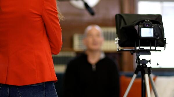 a scene from behind a video camera showing a business man being interviewed