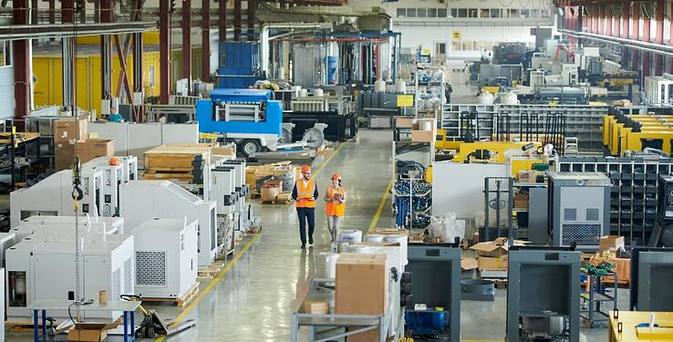 Colleagues walking manufacturing plant floor discussing current challenges