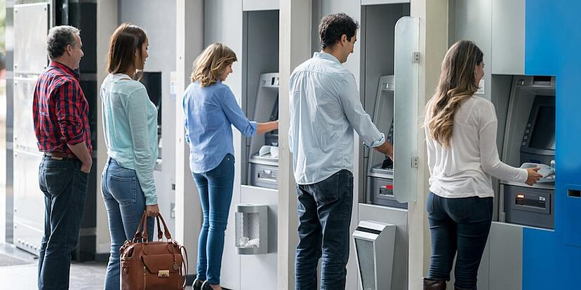 People taking out money at ATMs