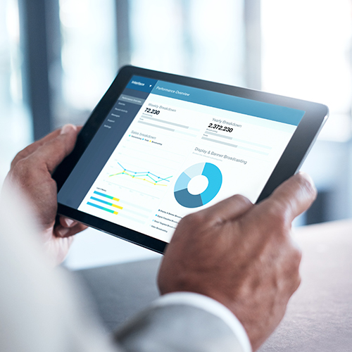 Person holding a tablet computer showing automation metrics